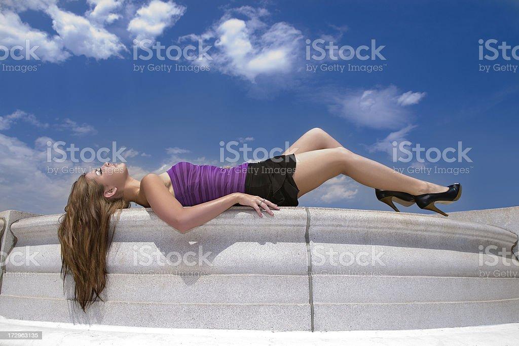 Beautiful Woman Lays on Limestone Wall stock photo