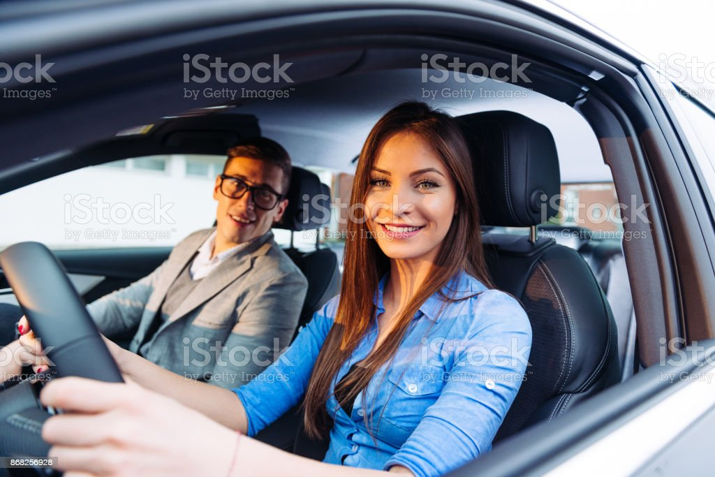 beautiful woman learning to drive a car with professional driving instructor stock photo