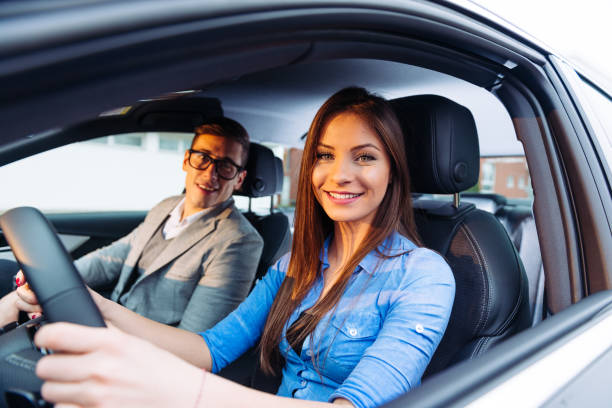 beautiful woman learning to drive a car with professional driving instructor Teenager or young woman learning to drive a car with driving instructor. Woman is confident and she is driving like a pro. driving instructor stock pictures, royalty-free photos & images