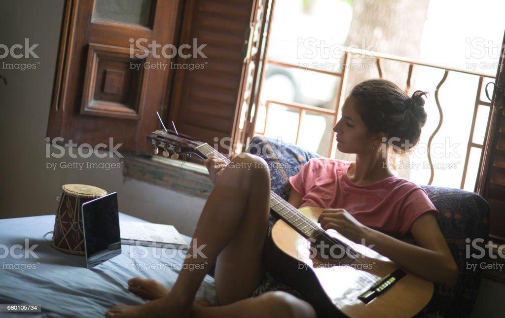 Linda mulher, aprender a tocar guitarra. - foto de acervo