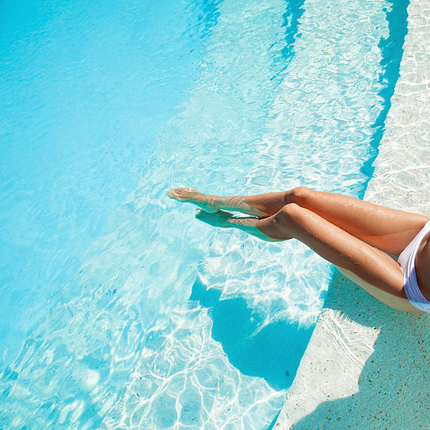 beautiful woman legs in swimming pool. - standing water stock pictures, royalty-free photos & images