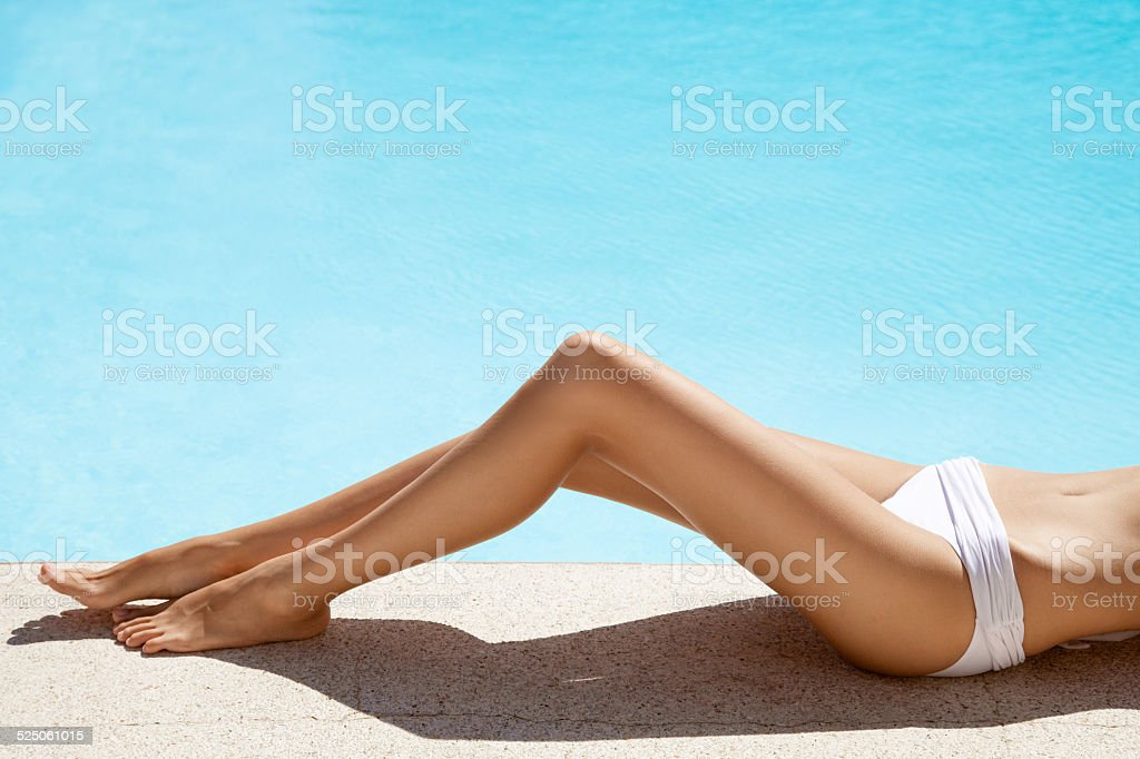 Beautiful woman legs. Sunbathing near swimming pool. stock photo
