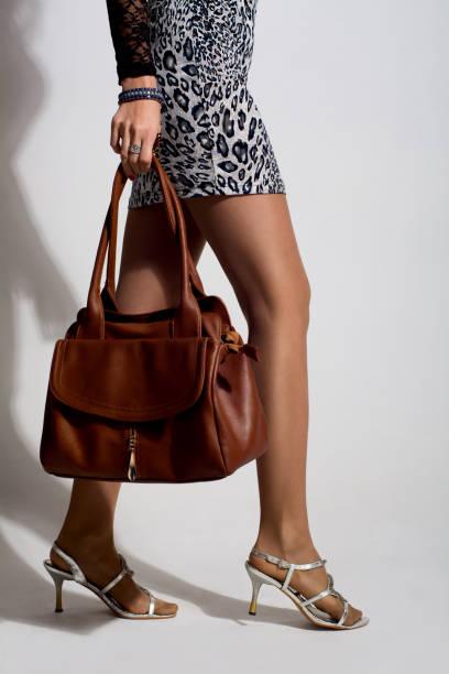 schöne frau beine mit eine braune tasche - damen rock braun stock-fotos und bilder
