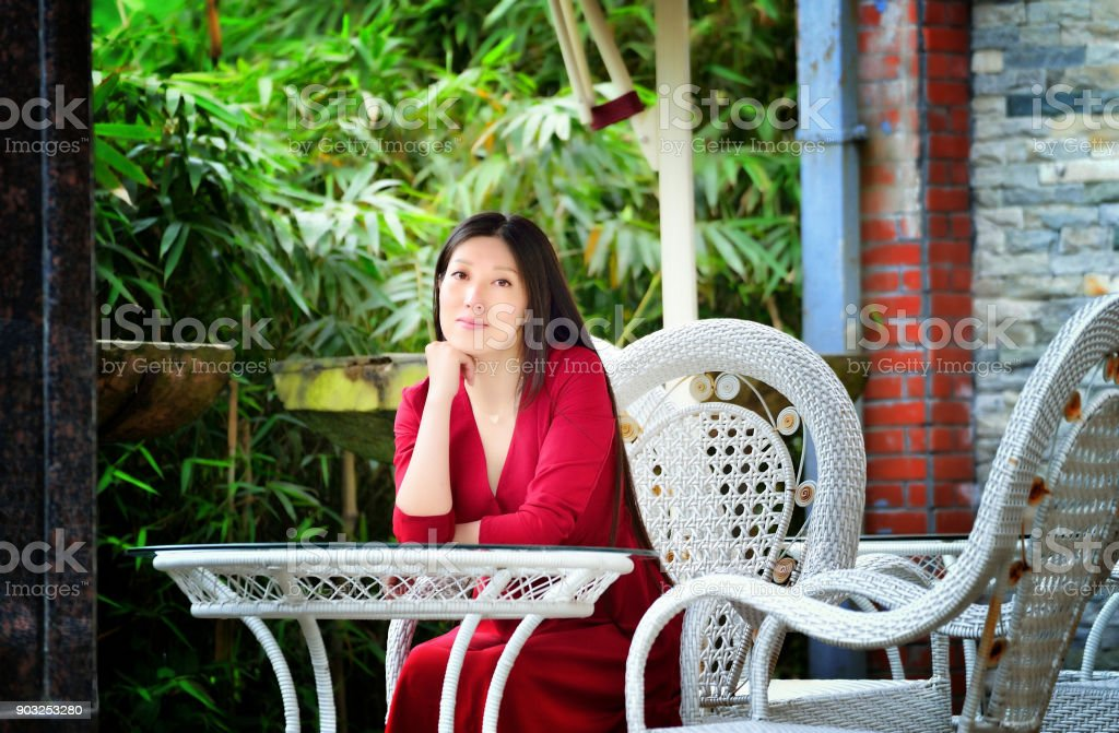 A beautiful woman leisurely sitting outside stock photo