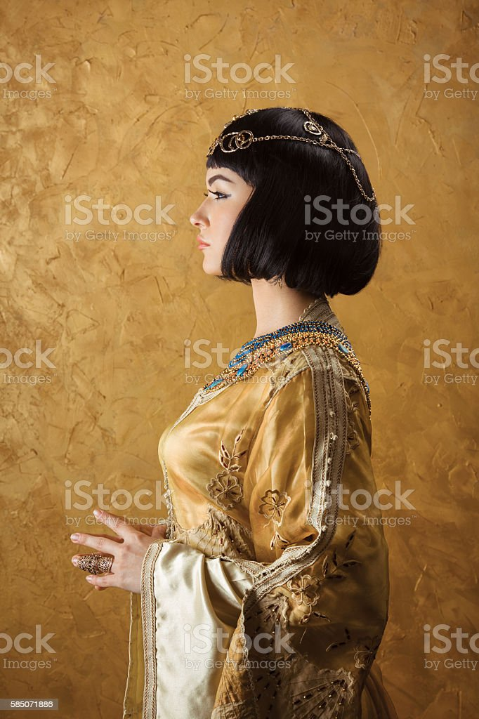 Beautiful woman like Egyptian Queen Cleopatra on golden background. Side stock photo