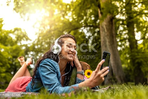 Pretty young woman lying on a picnic blanket at the park, listening to music