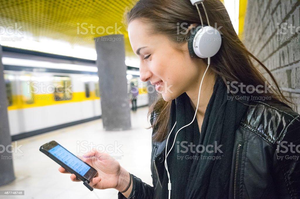 Beautiful Woman Listening Music On Her Smartphone, Subway Train Background stock photo