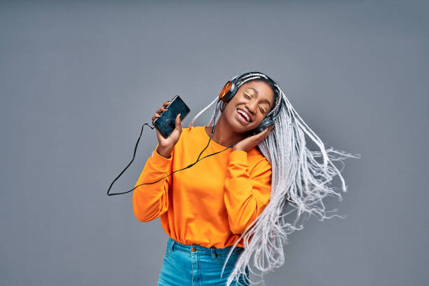 Beautiful woman listening music with her headphones and dancing. stock photo