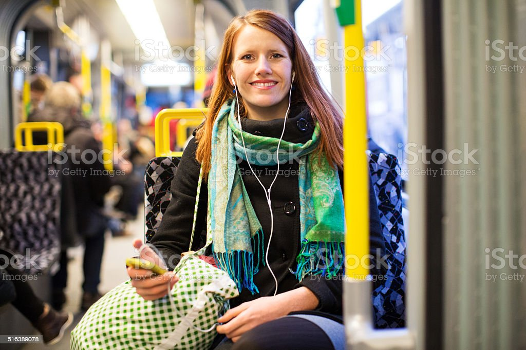 Beautiful woman listening to music from her phone on train stock photo