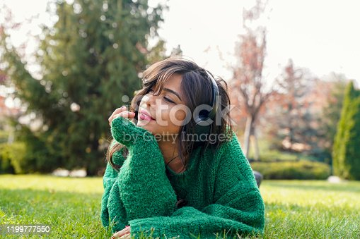 969233490 istock photo beautiful woman listening to music in the park 1199777550