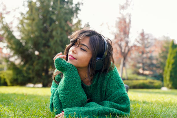 beautiful woman listening to music in the park stock photo