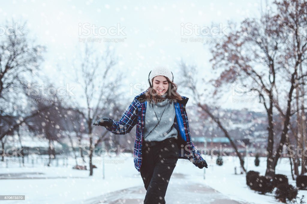 Beautiful woman listening to music on a winter day stock photo