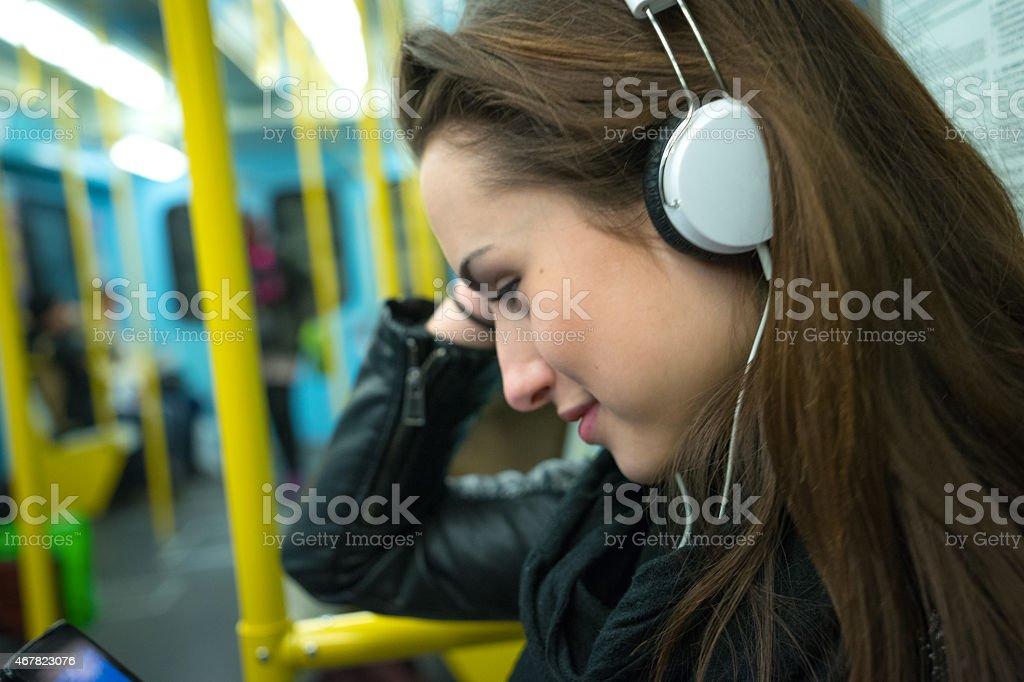 Beautiful Woman Listening To Music On Subway Train stock photo