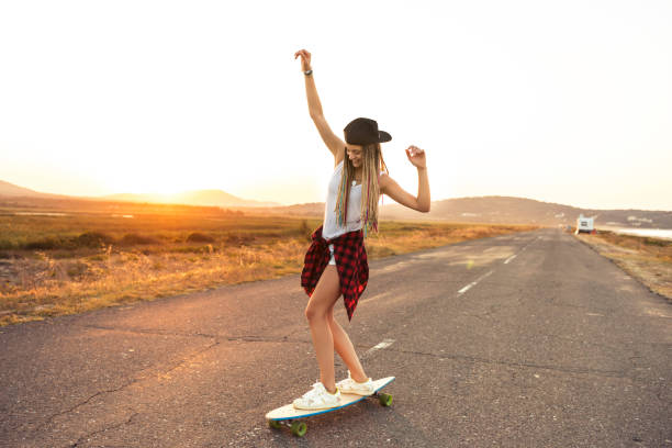 Beautiful woman longboarding on country road stock photo