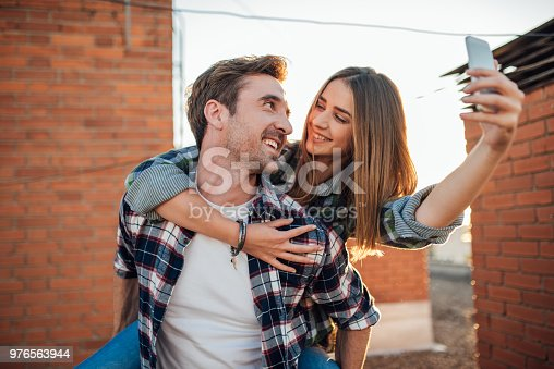636330566istockphoto Beautiful woman looking at a man while taking a selfie 976563944