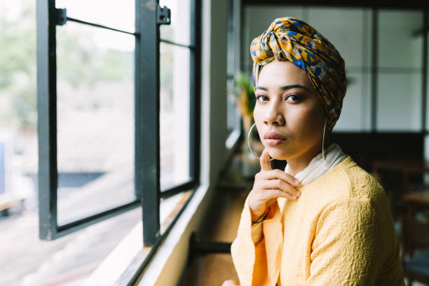 Beautiful Woman Looking at Camera Beautiful woman contemplating in a cafe. headscarf stock pictures, royalty-free photos & images
