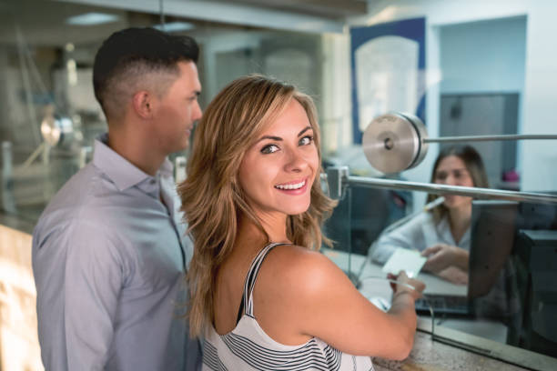 Olhando para o pé de câmera ao lado de seu parceiro no escritório de caixa pronto para assistir a um filme de mulher bonita - foto de acervo
