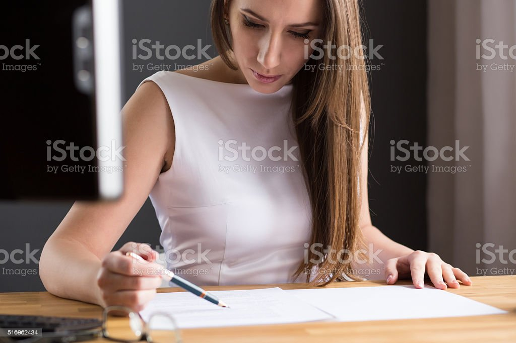 Beautiful woman looking at contract at the desk stock photo