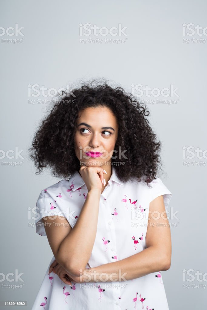 Beautiful woman looking at copy space Close up of beautiful young woman with curly hair looking away at copy space with her hand on chin on white background 20-24 Years Stock Photo