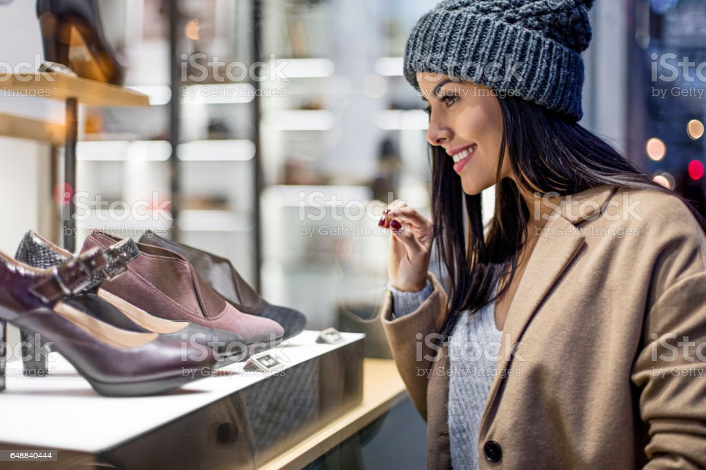 Beautiful woman looking at high heels in store stock photo