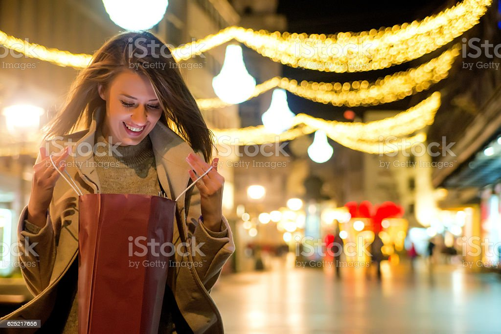Beautiful woman looking at shopping bag during christmas time stock photo