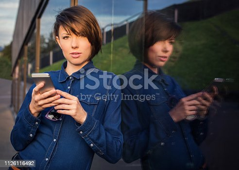 beautiful woman with phone  looking at the camera in the city