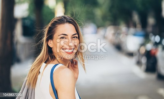 Beautiful woman looking back over her shoulder on the street