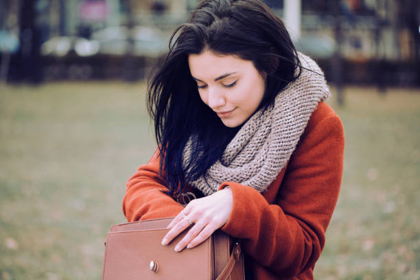 Beautiful woman looking for something in her purse stock photo