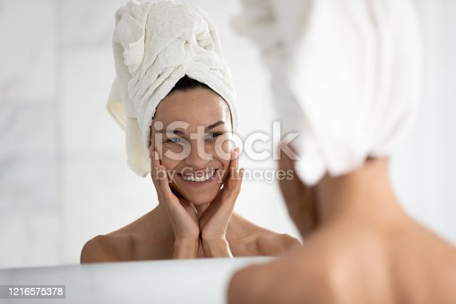 532331272 istock photo Beautiful woman looking in mirror touches ideal skin feels happy 1216575378