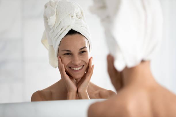 de mooie vrouw die in spiegel kijkt raakt ideale huid voelt gelukkig - mirror mask stockfoto's en -beelden