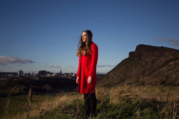 Beautiful woman looking into distance with Edinburgh skyline behind her. stock photo
