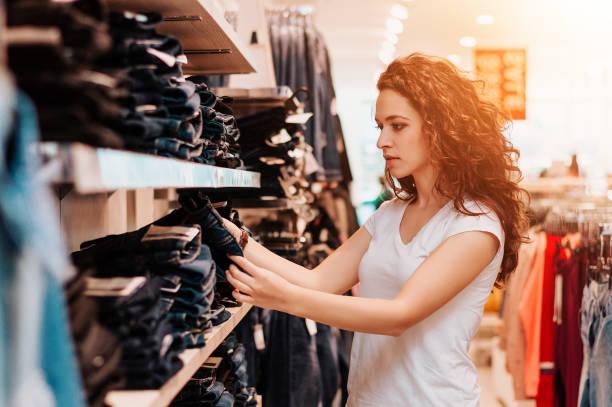 schöne frau, die jeans in der boutique. - damen jeans sale stock-fotos und bilder