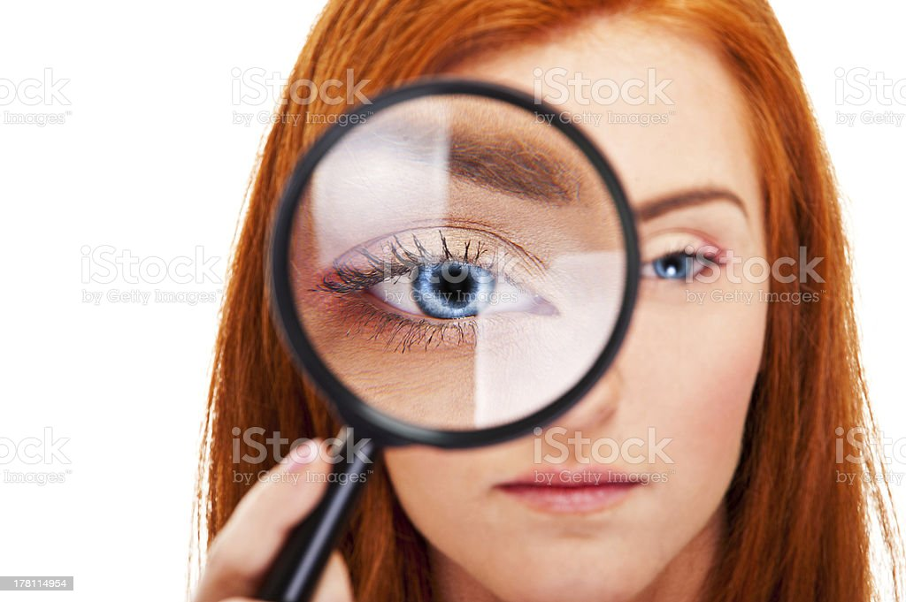 Beautiful woman looking through a magnifying glass stock photo