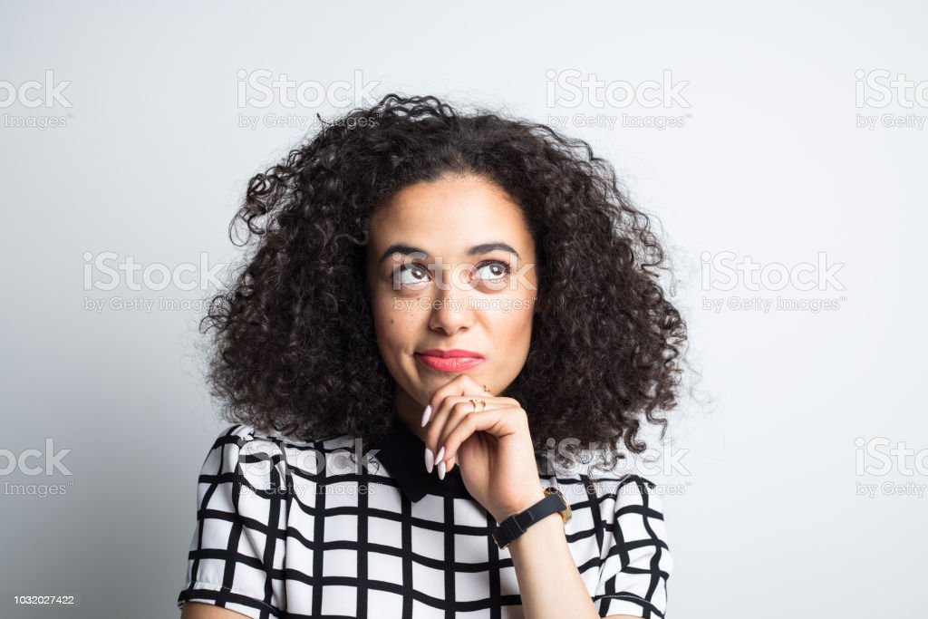 Beautiful woman looking up and thinking Close up of beautiful young woman with curly hair looking up at copy space with hand on chin and thinking 20-24 Years Stock Photo