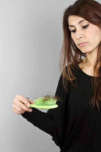 Schöne Frau, deren Haare auf Haarbürste – Foto