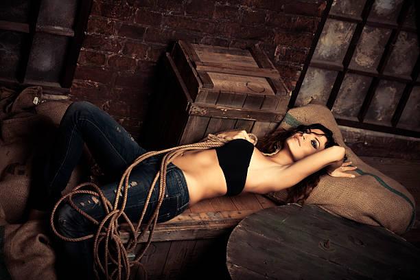 schöne frau entspannung in verlassenen warehouse - leinenhosen frauen stock-fotos und bilder
