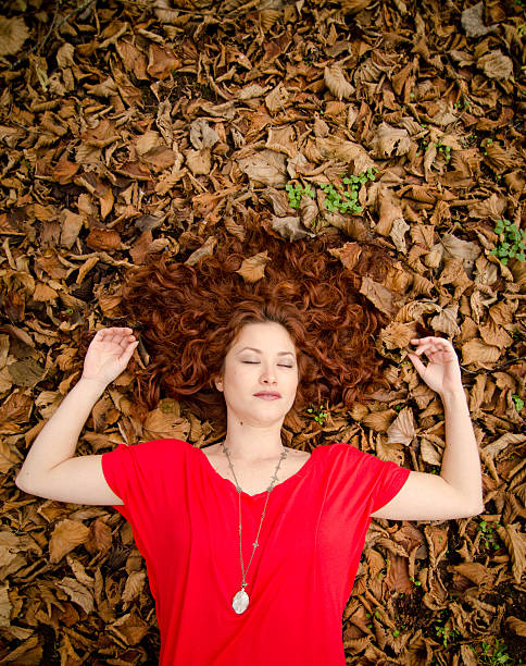 beautiful woman lying in the leaves - woman green eyes red hair stock photos and pictures