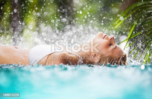 Side view of a beautiful woman lying in the tropical pool  while the rain is pouring.