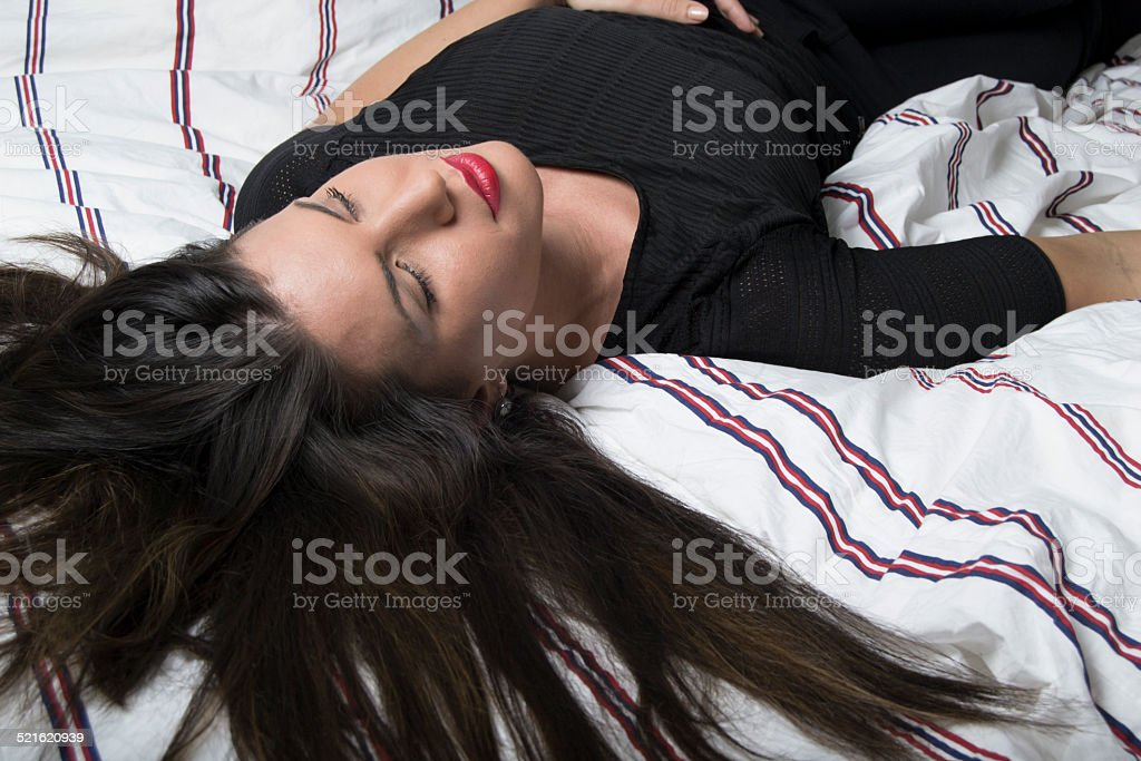 Beautiful woman lying on a bed (dreaming, sleeping, meditating) stock photo