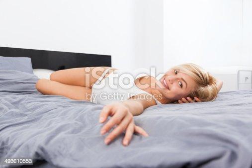 607490114istockphoto Beautiful woman lying on bed home 493610553