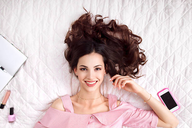 beautiful woman lying on bed top view - marvel schlafzimmer stock-fotos und bilder