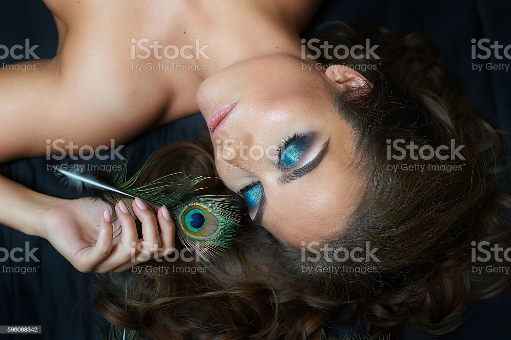 beautiful woman lying on bed with peacock feather and makeup royalty-free stock photo
