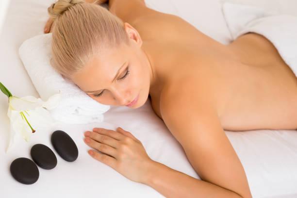 Beautiful woman lying on massage bed at spa stock photo