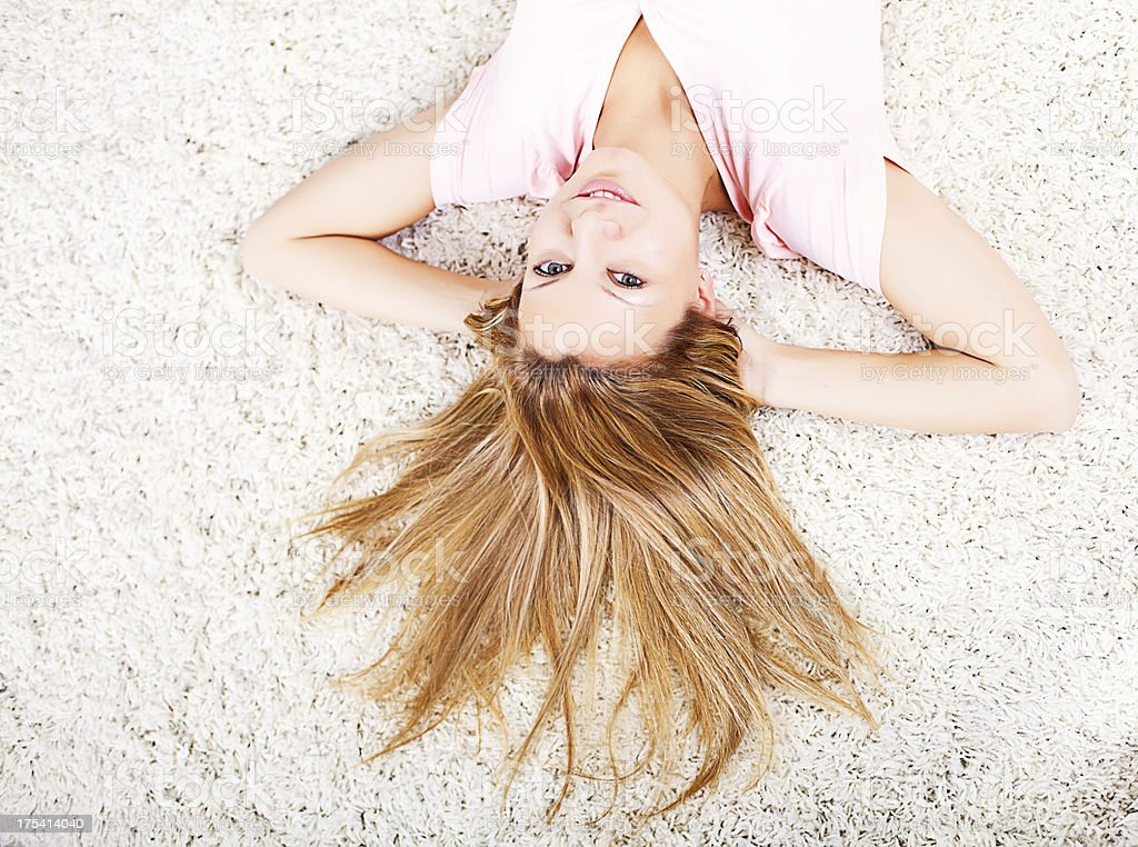 Beautiful woman lying on the carpet at home royalty-free stock photo