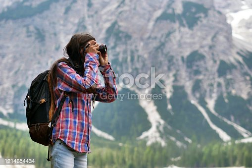 A beautiful woman makes trekking and explores the nature around her. The woman is happy and enthusiastic about the landscape around her and admires him. Concept of: freedom, exploration, breath