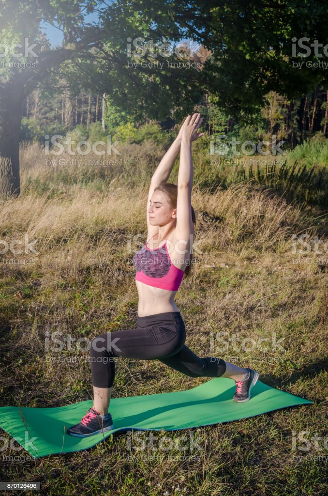 Beautiful woman making exercises on field road during stock photo