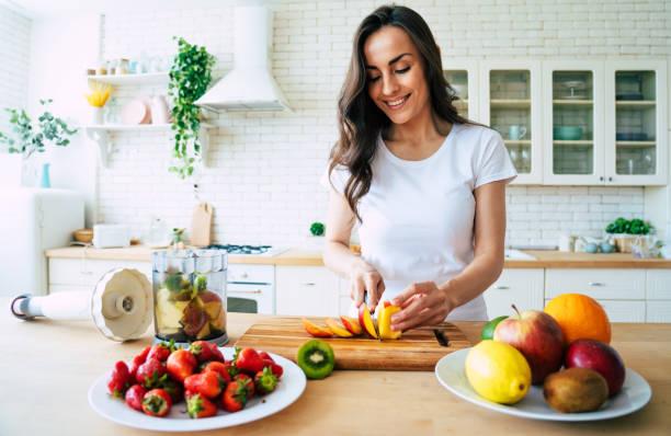 bella donna che fa frullati di frutta con frullatore. - cucinare foto e immagini stock