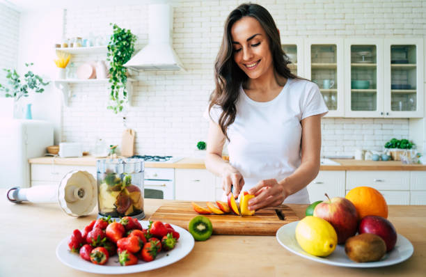Beautiful woman making fruits smoothies with blender. Healthy eating lifestyle concept portrait of beautiful young woman preparing drink with bananas, strawberry and kiwi at home in kitchen. preparing food stock pictures, royalty-free photos & images