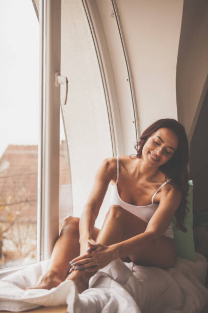 Beautiful woman massaging legs by the window Happy Caucasian woman is massaging her legs during skin care routine at home. human leg stock pictures, royalty-free photos & images