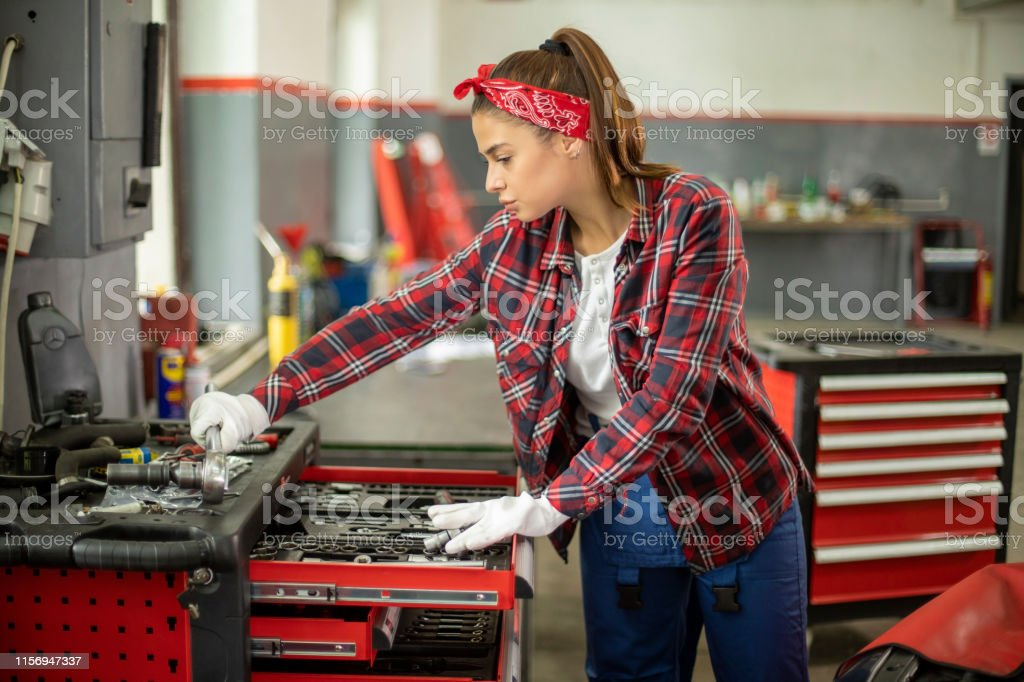 Portrait of young, beautiful and proud female mechanic solving...